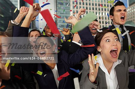Businesspeople cheering as ticker tape falls Stock Photo - Premium Royalty-Free, Image code: 614-06402721