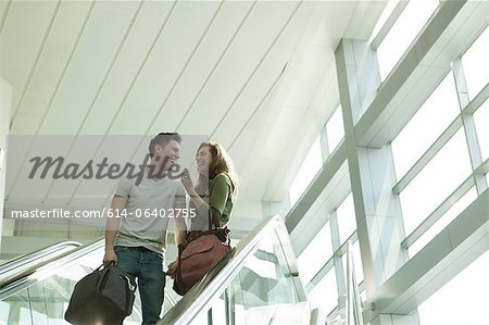 Young couple travelling on escalator Stock Photo - Premium Royalty-Free, Image code: 614-06402755