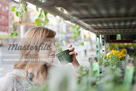 Young woman smelling a plant Stock Photo - Premium Royalty-Free, Image code: 614-06402773