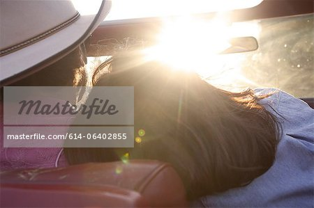 Woman resting head on boyfriend's shoulder as he drives in sunlight Stock Photo - Premium Royalty-Free, Image code: 614-06402855