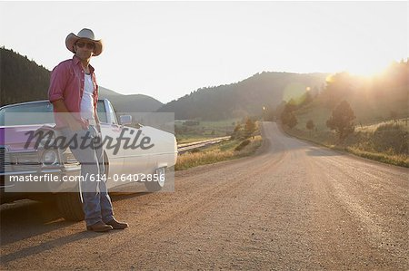 Man in cowboy hat, leaning against convertible car Stock Photo - Premium Royalty-Free, Image code: 614-06402856