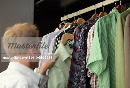 Man taking shirt from wardrobe Stock Photo - Premium Royalty-Free, Image code: 614-06402955