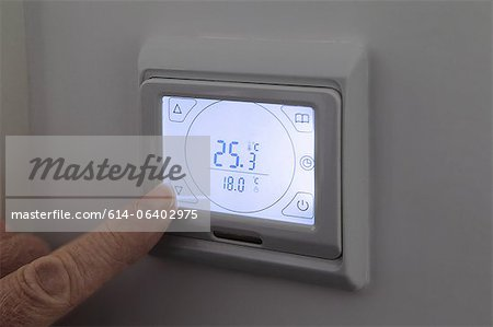 Person adjusting digital thermostat Stock Photo - Premium Royalty-Free, Image code: 614-06402975