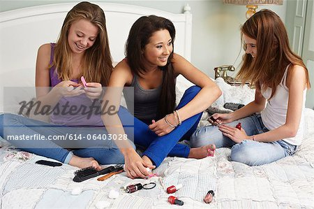 Teenage girls using nail polishes Stock Photo - Premium Royalty-Free, Image code: 614-06403028