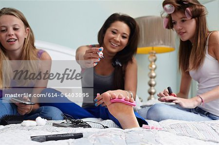 Teenage girls painting toenails Stock Photo - Premium Royalty-Free, Image code: 614-06403095