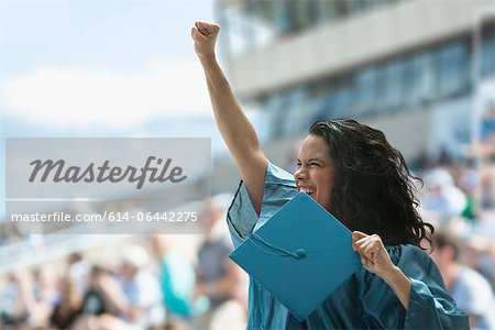Female graduate raising fist Stock Photo - Premium Royalty-Free, Image code: 614-06442275