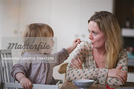 Daughter spoon feeding mother Stock Photo - Premium Royalty-Free, Image code: 614-06442296