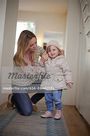 Mother putting knit hat on daughter Stock Photo - Premium Royalty-Free, Image code: 614-06442301