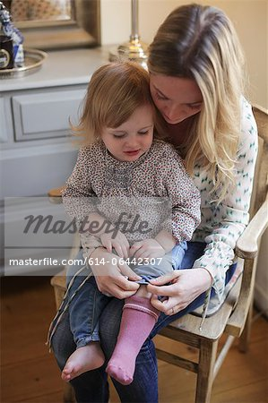 Mother helping daughter put on socks Stock Photo - Premium Royalty-Free, Image code: 614-06442307