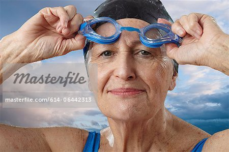 Senior woman adjusting swimming goggles Stock Photo - Premium Royalty-Free, Image code: 614-06442313