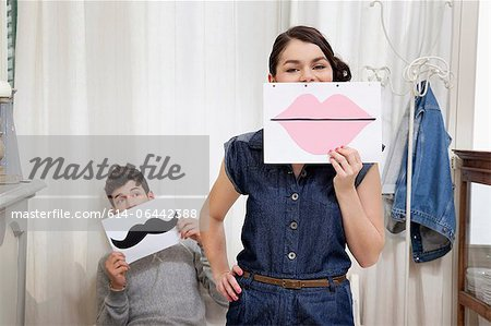 Couple holding lips and moustache Stock Photo - Premium Royalty-Free, Image code: 614-06442388