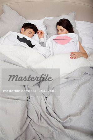 Couple in bed with lips and moustache Stock Photo - Premium Royalty-Free, Image code: 614-06442402