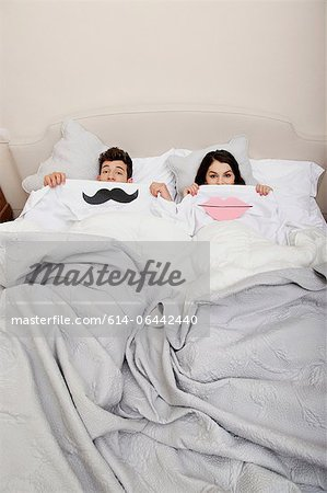 Couple in bed with lips and moustache Stock Photo - Premium Royalty-Free, Image code: 614-06442440