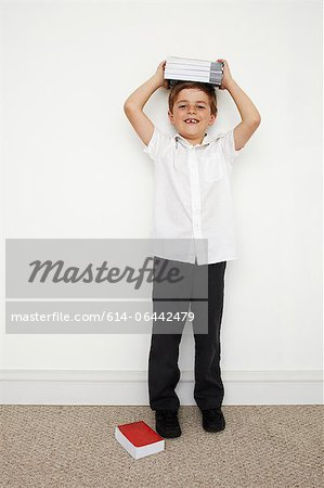 Schoolboy holding books on his head Stock Photo - Premium Royalty-Free, Image code: 614-06442479