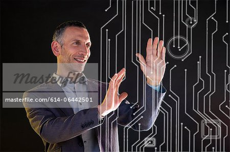 Businessman touching virtual circuit board symbols Stock Photo - Premium Royalty-Free, Image code: 614-06442501