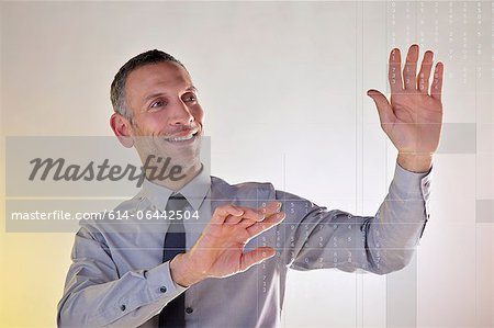 Businessman using virtual data Stock Photo - Premium Royalty-Free, Image code: 614-06442504