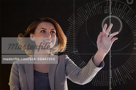 Businesswoman touching digital symbol Stock Photo - Premium Royalty-Free, Image code: 614-06442506