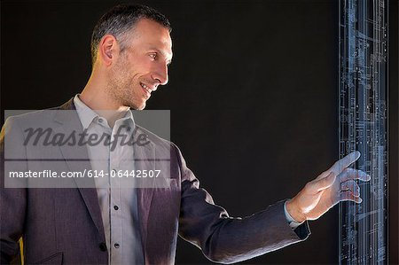 Businessman touching virtual information Stock Photo - Premium Royalty-Free, Image code: 614-06442507