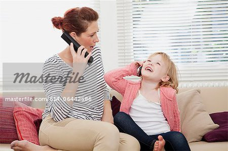 Mother and daughter on cell phones Stock Photo - Premium Royalty-Free, Image code: 614-06442586