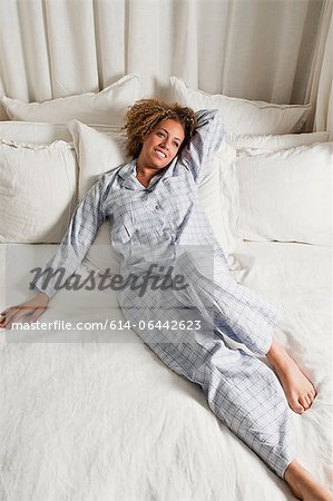 Woman wearing pyjamas reclining in bed Stock Photo - Premium Royalty-Free, Image code: 614-06442623