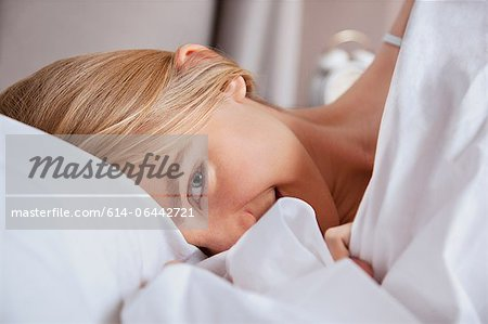 Close up of young woman in bed Stock Photo - Premium Royalty-Free, Image code: 614-06442721