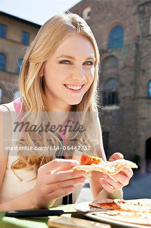 Young woman at restaurant outdoors with slice of pizza Stock Photo - Premium Royalty-Free, Image code: 614-06442732
