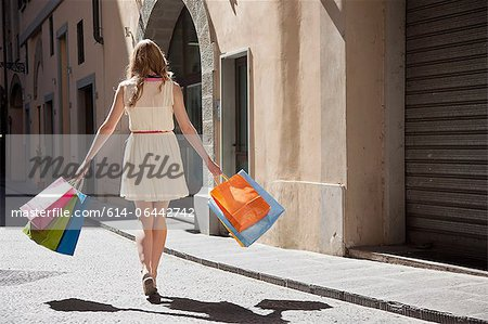 Rear view of young woman on street with shopping bags Stock Photo - Premium Royalty-Free, Image code: 614-06442742