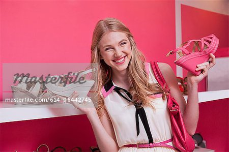 Happy young woman holding shoes in store Stock Photo - Premium Royalty-Free, Image code: 614-06442745