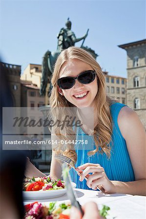 Young woman having salad at restaurant outdoors Stock Photo - Premium Royalty-Free, Image code: 614-06442758