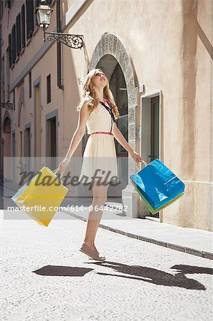 Young woman on street with shopping bags, looking up Stock Photo - Premium Royalty-Free, Image code: 614-06442782