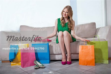Young woman sitting on sofa with shopping bags Stock Photo - Premium Royalty-Free, Image code: 614-06442790