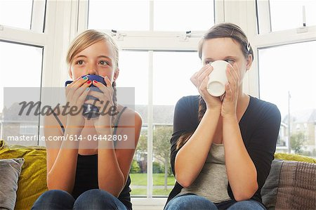 Two girls drinking hot drinks Stock Photo - Premium Royalty-Free, Image code: 614-06442809