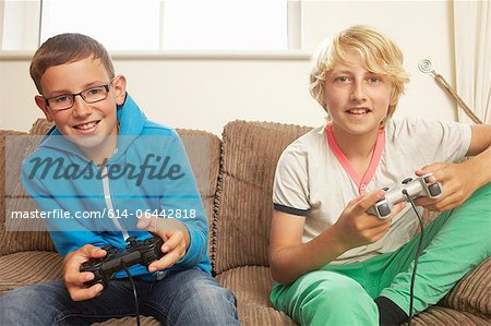 Two boys playing video game Stock Photo - Premium Royalty-Free, Image code: 614-06442818