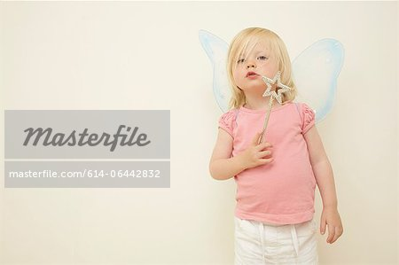 Toddler wearing wings, holding wand Stock Photo - Premium Royalty-Free, Image code: 614-06442832