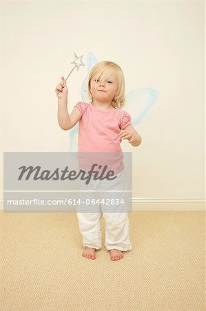 Toddler wearing wings, holding wand Stock Photo - Premium Royalty-Free, Image code: 614-06442834