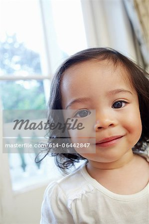 Portrait of a little girl smiling at camera Stock Photo - Premium Royalty-Free, Image code: 614-06442847