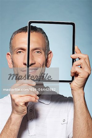 Man covering half his face with digital tablet Stock Photo - Premium Royalty-Free, Image code: 614-06442882
