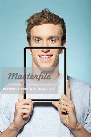 Man covering half his face with digital tablet Stock Photo - Premium Royalty-Free, Image code: 614-06442916