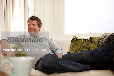 Man relaxing on sofa Stock Photo - Premium Royalty-Free, Image code: 614-06442992