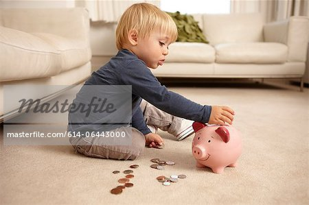Boy putting coins in piggy bank Stock Photo - Premium Royalty-Free, Image code: 614-06443000