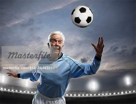 Senior man playing football Stock Photo - Premium Royalty-Free, Image code: 614-06443061