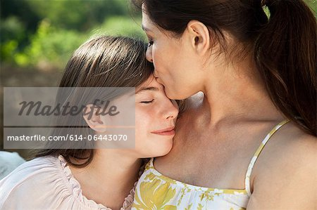 Portrait of mother kissing daughter on forehead Stock Photo - Premium Royalty-Free, Image code: 614-06443070