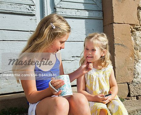 Two sisters, one touching others face Stock Photo - Premium Royalty-Free, Image code: 614-06443081