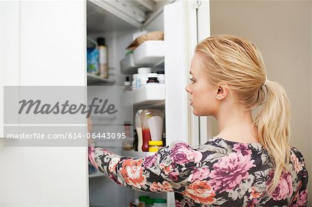 Young woman looking in refrigerator Stock Photo - Premium Royalty-Free, Image code: 614-06443095