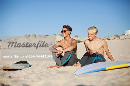 Two young surfers sitting on a beach Stock Photo - Premium Royalty-Free, Image code: 614-06443108