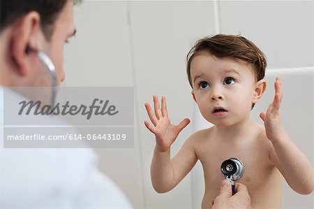 Doctor using stethoscope to check little boy Stock Photo - Premium Royalty-Free, Image code: 614-06443109