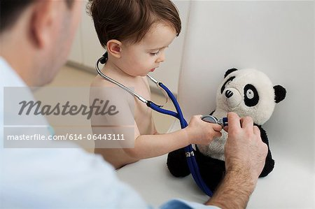 Little boy and doctor using stethoscope on panda toy Stock Photo - Premium Royalty-Free, Image code: 614-06443111