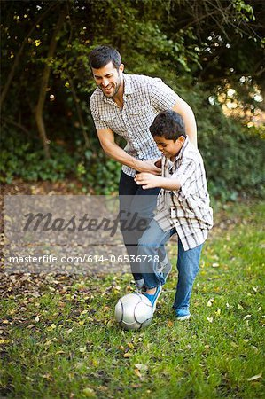 Father and son playing soccer together Stock Photo - Premium Royalty-Free, Image code: 614-06536728
