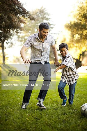 Father and son playing soccer together Stock Photo - Premium Royalty-Free, Image code: 614-06536730