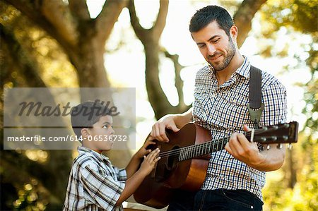 Father and son playing guitar together Stock Photo - Premium Royalty-Free, Image code: 614-06536732